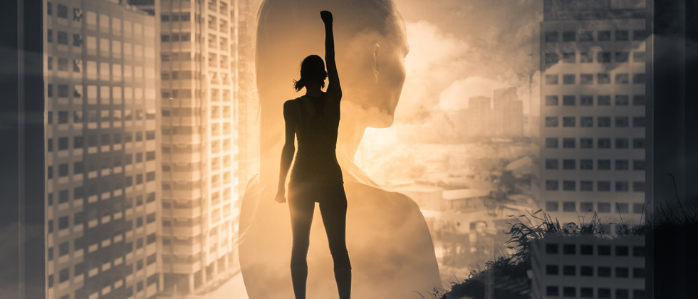 A woman with her fist up to show she is powerful while in front of a skyline