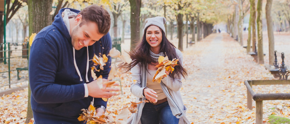 An attractive couple playing in the fall leaves together