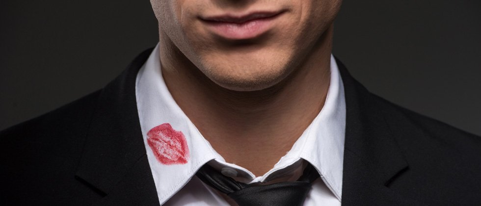 A guy with a big red lipstick stain on the collar of his shirt