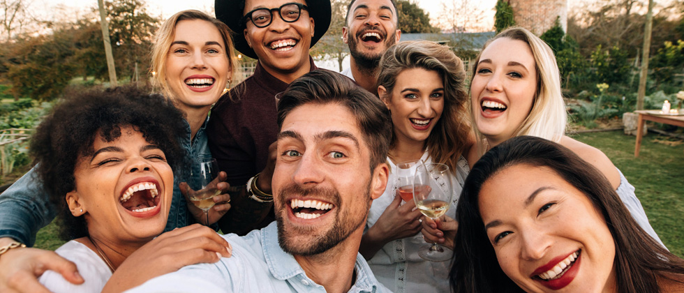 A group of friends outside laughing and drinking wine