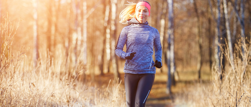 A female runner jogging on a wooded path in the sun
