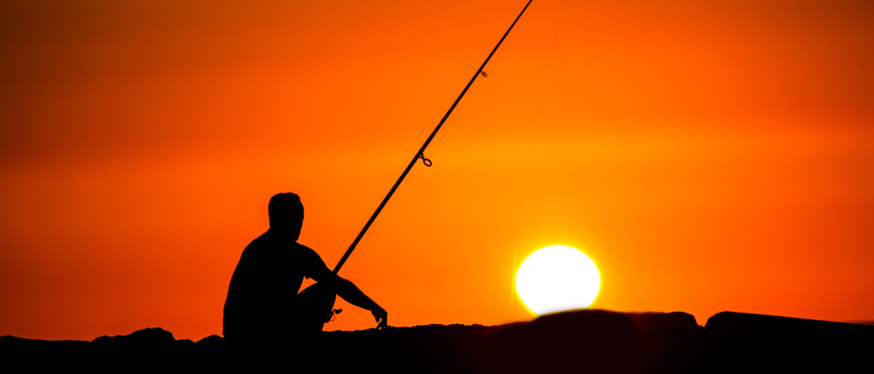 A man sitting next to a body of water fishing at sunset