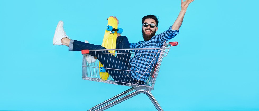 A guy sitting in a shopping cart with a skateboard