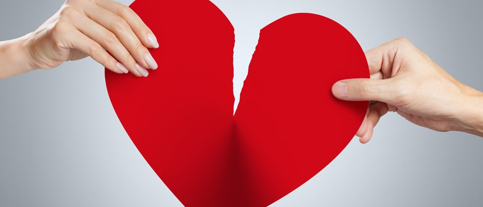 A big paper heart being riped by two people pulling at it
