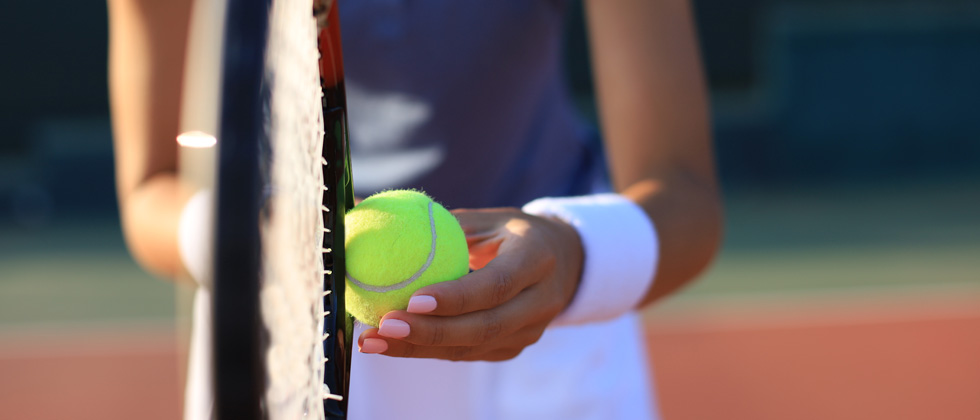 A woman on a tennis court getting ready to serve