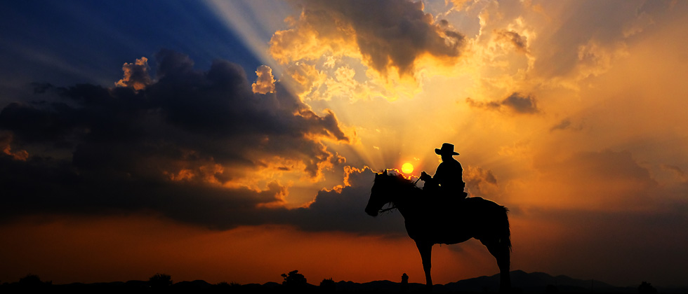 A person in a cowboyhat sitting on a horse in the middle of a sunset