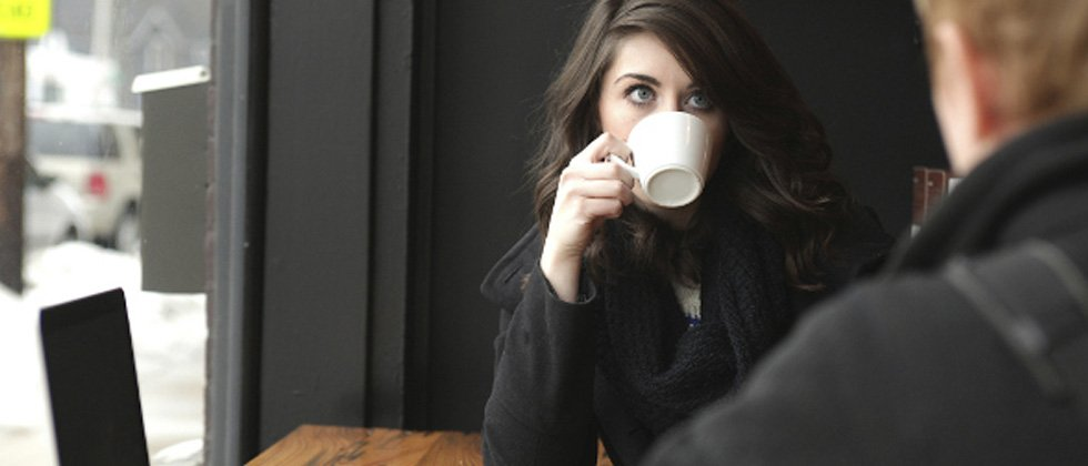 Woman drinking from a coffee mug while having an intense conversation