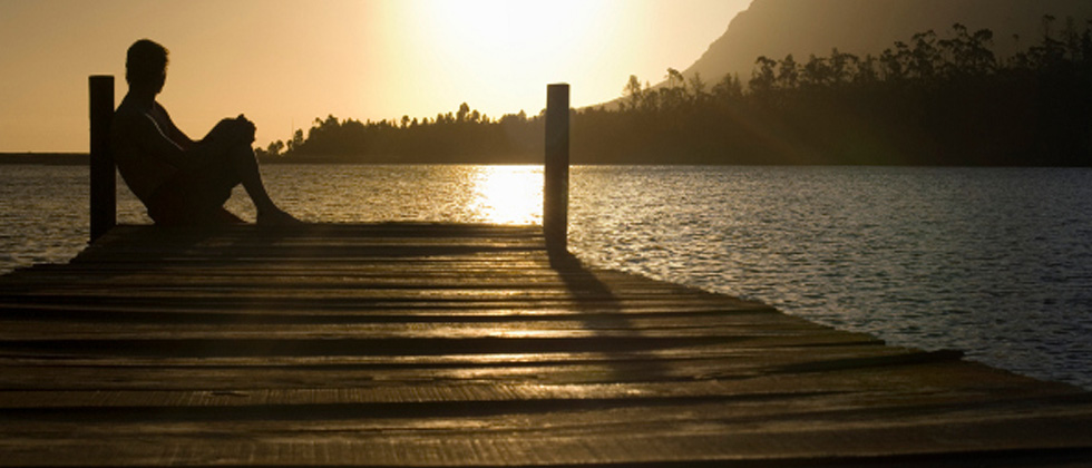 A man sitting at the edge of the dock reflecting at sunset