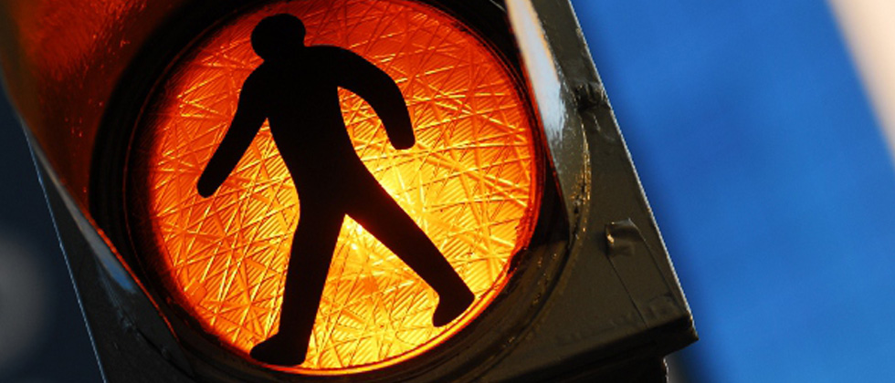 A pedestrian walk symbol showing for people to slow