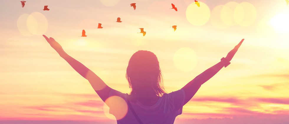 A woman with her arms open looking into the sunset with birds flying