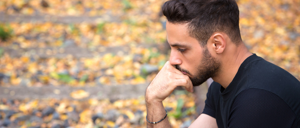 A man sitting on the side of the road looking very upset