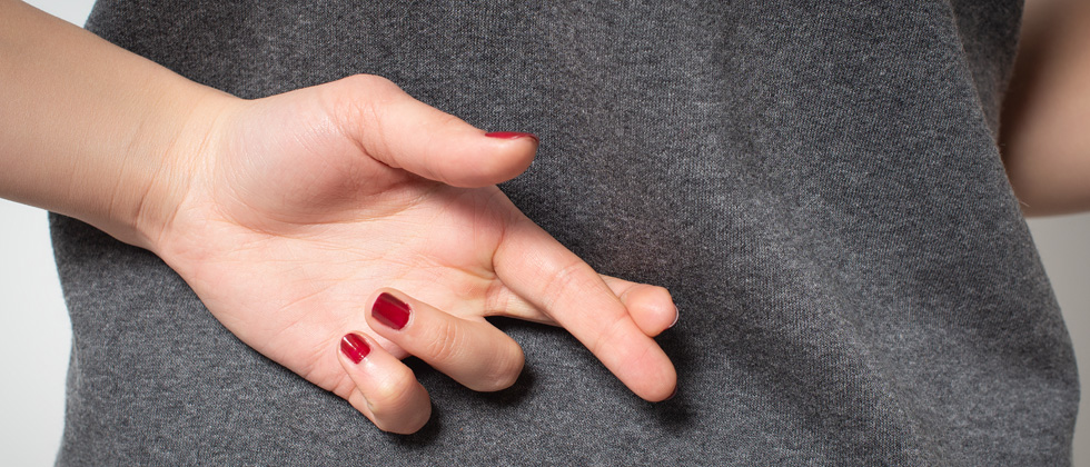 A woman crossing her fingers behind her back