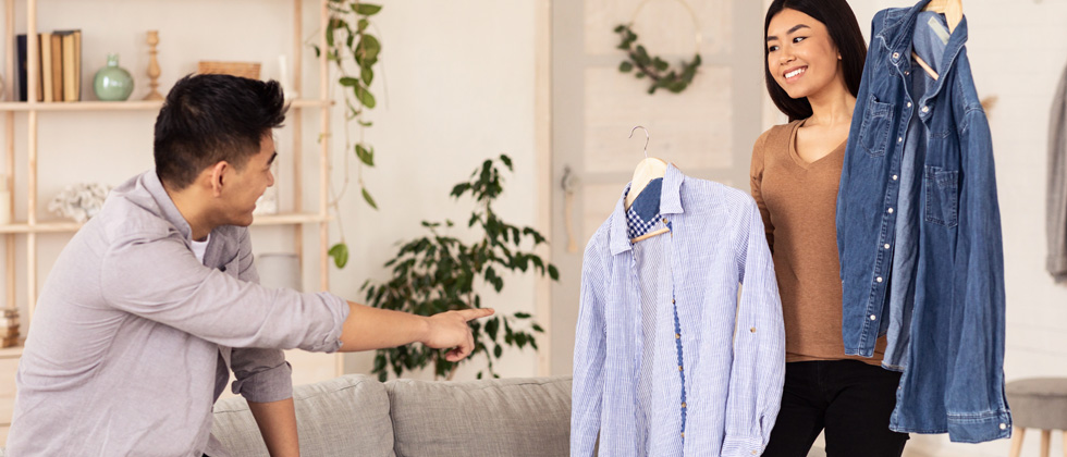A woman helping her boyfriend pick up a collared shirt to wear