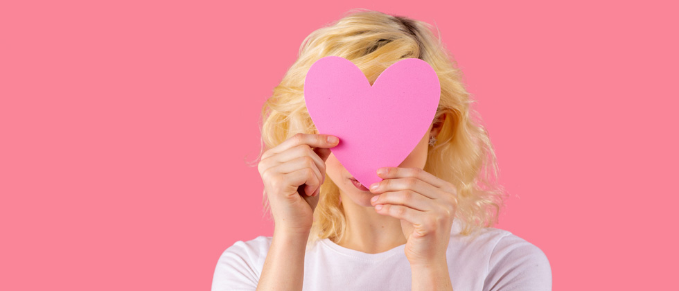 A woman holding a pink cutout heart over her face