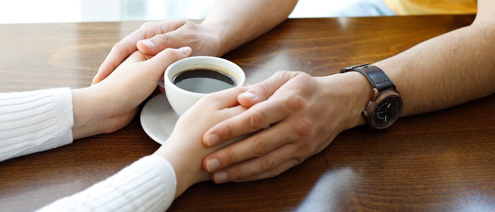 A woman holding her coffee with her boyfriend's hands around hers
