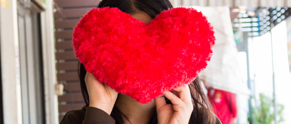 Someone covering their face with a big red heart-shaped pillow