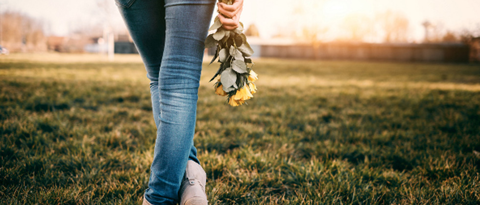 Someone walking in an empty grass field holding yellow roses