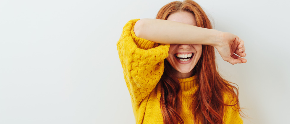 A redhaired woman laughing so hard she's covering her eyes