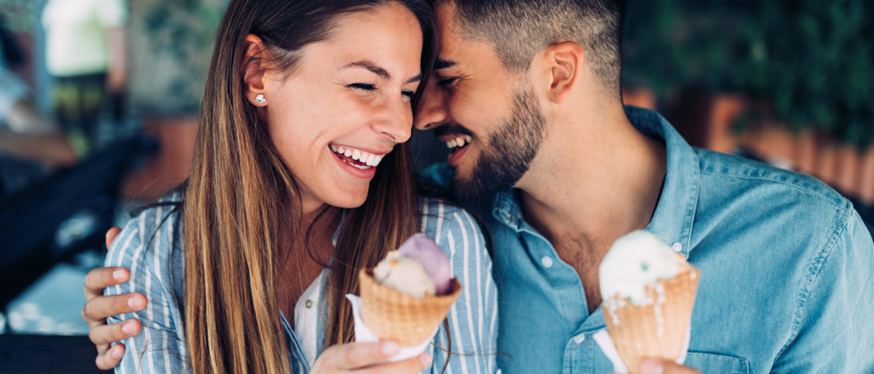 A cute couple flirting while eating ice cream cones together