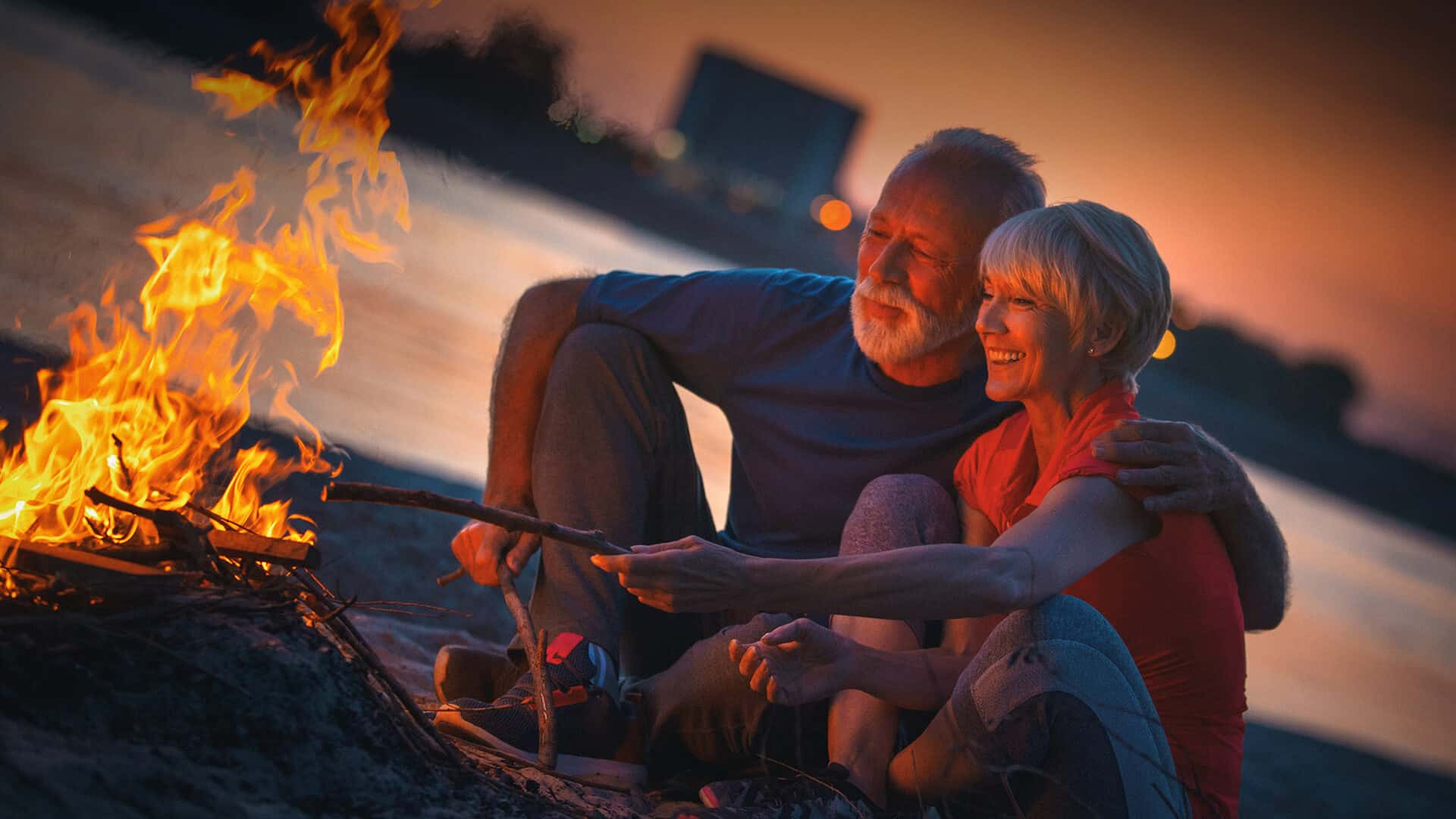 60s dating symbolized by a happy couple sitting in front of a campfire in Canada