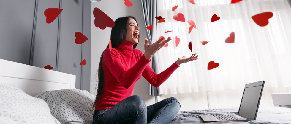 A woman sitting on her bed in front of her laptop throwing paper hearts