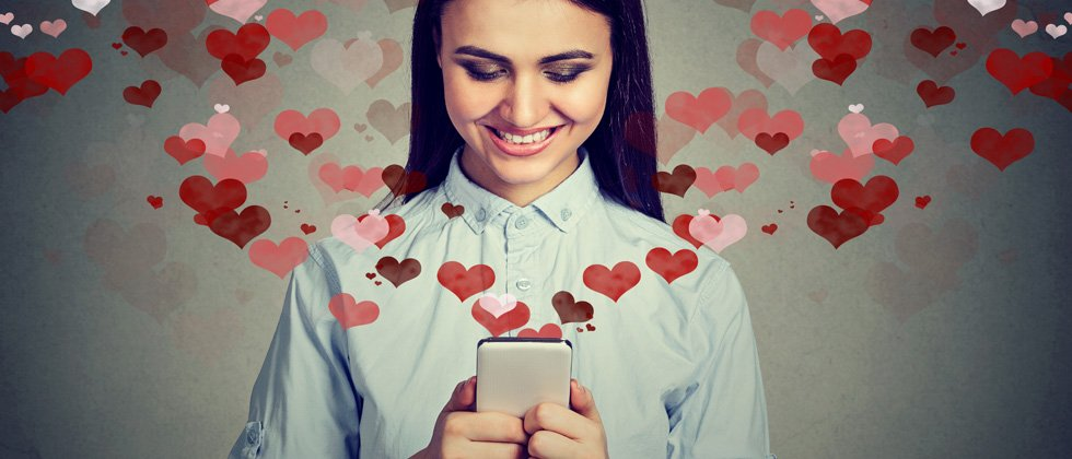 A woman smiling & holding her phone with dozens of hearts flying out of it