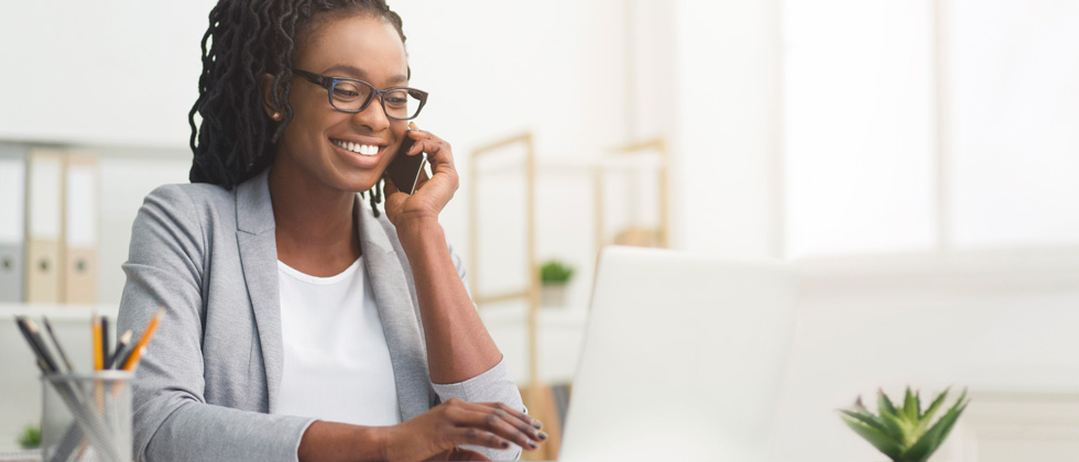 A woman talking on the phone while working on her laptop at her desk