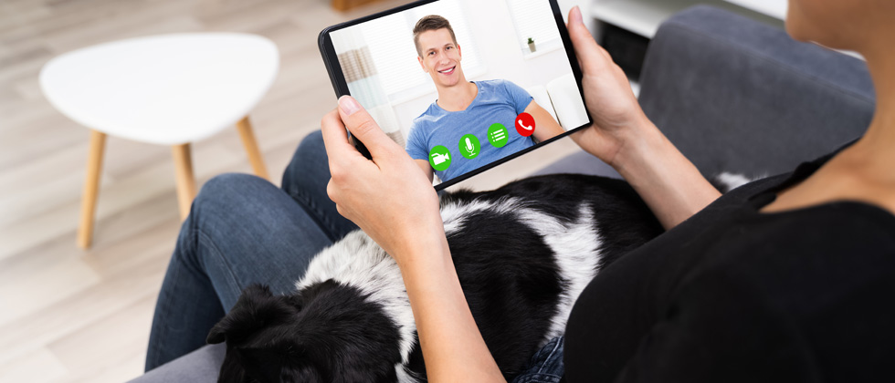 A woman video chatting with a guy while her dog lays on her lap