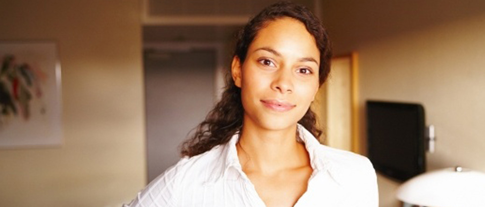 A woman standing in her apartment slightly smiling into the camera