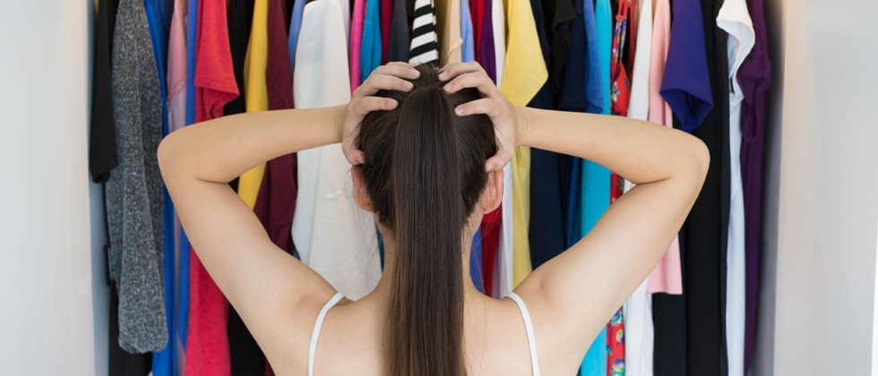 Woman standing in front of her closet not knowing what to wear
