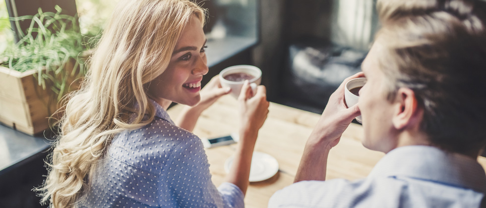 Beautiful smiling girl drinking coffee talking to a young man