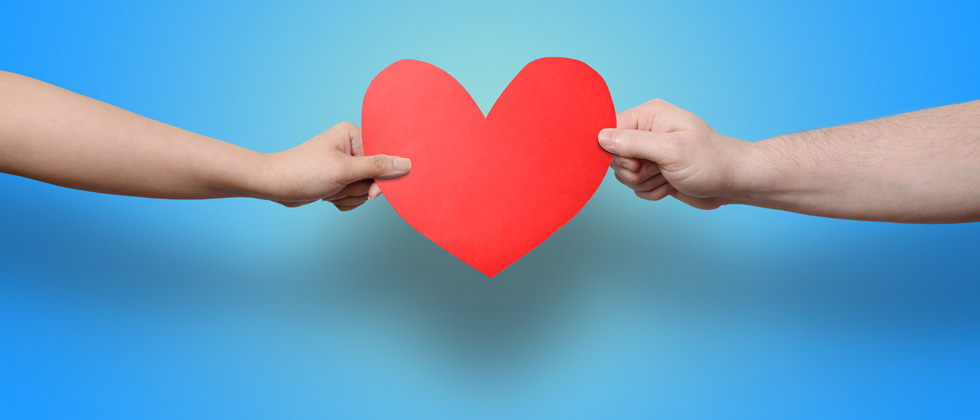Two people grabbing at a big paper heart at each end