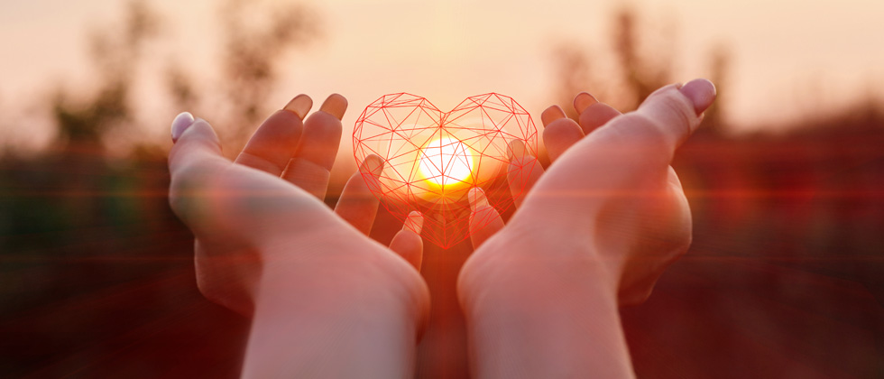 Someone holding up a wireframed heart with the sun in the middle of it