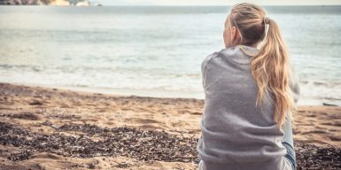 Woman looks at the sea and wonders why love hurts so much